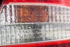 Opinión cercana de la linterna posterior moderna del coche con las gotitas en ella fotos de archivo