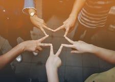 Opinión cercana los amigos jovenes de la gente con las pilas que muestran la unidad y imagen de archivo