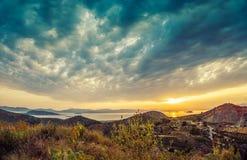 Opinión colorida de la puesta del sol de montañas y mar y nubes dramáticas encendido Fotografía de archivo