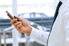 Opinión cosechada el hombre de negocios que sostiene el teléfono móvil que coloca en frente la ventana imagenes de archivo