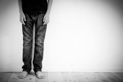 Opinión cosechada el niño descalzo cerca de la pared Imagen de archivo libre de regalías
