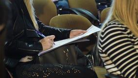 Opinión cosechada la mujer joven que hace notas en la reunión de negocios almacen de metraje de vídeo