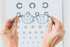 opinión cosechada la persona que sostiene los vidrios con el ojo imágenes de archivo libres de regalías