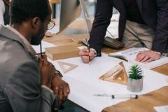 opinión cosechada los arquitectos multiétnicos que discuten y que dibujan modelos fotos de archivo