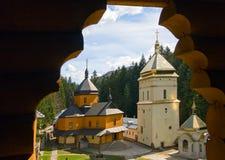 Opinión cristiana del monasterio a través de la ventana de madera Imagen de archivo libre de regalías