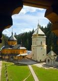 Opinión cristiana del monasterio a través de la ventana de madera Foto de archivo