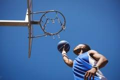 Opinión de ángulo bajo el adolescente que juega a baloncesto Foto de archivo