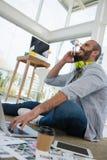 Opinión de ángulo bajo el diseñador que habla en el teléfono móvil mientras que se sienta en piso Fotografía de archivo