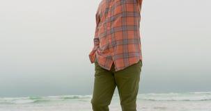 Opinión de ángulo bajo el hombre afroamericano mayor activo con la mano en bolsillo que camina en la playa 4k almacen de metraje de vídeo
