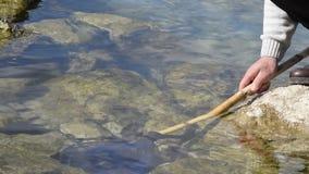 Opinión de ángulo bajo el hombre en la roca del mar con la red de pesca en el agua