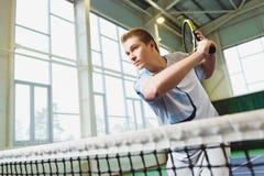 Opinión de ángulo bajo el hombre joven resuelto que juega al tenis interior Fotos de archivo