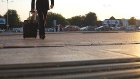 Opinión de ángulo bajo el hombre de negocios joven irreconocible que va al aeropuerto y que tira de la maleta en las ruedas en la almacen de metraje de vídeo