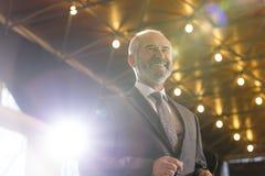 Opinión de ángulo bajo el hombre de negocios mayor sonriente en la situación del traje contra el tejado iluminado fotos de archivo