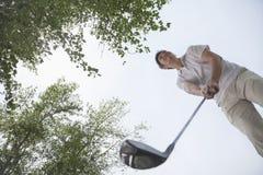 Opinión de ángulo bajo el hombre que consigue lista para golpear la pelota de golf en el campo de golf Imagen de archivo libre de regalías