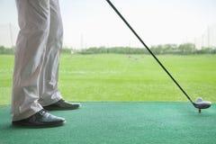 Opinión de ángulo bajo el hombre que consigue lista para golpear una pelota de golf Imagen de archivo libre de regalías