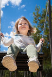 Opinión de ángulo bajo el niño que balancea en el parque Imágenes de archivo libres de regalías