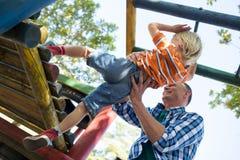 Opinión de ángulo bajo el padre que ayuda al hijo en jugar en el gimnasio de selva fotos de archivo libres de regalías