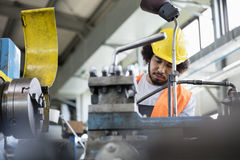 Opinión de ángulo bajo el trabajador manual joven que trabaja en la maquinaria en industria de metal imagen de archivo libre de regalías