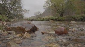 Opinión de ángulo bajo de la cama de la roca de la cama de río de las caídas de Steall en otoño metrajes