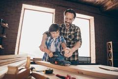 Opinión de ángulo bajo de la fijación trabajadora alegre creativa agradable del papá del amo de la persona dos que crea reparando fotografía de archivo