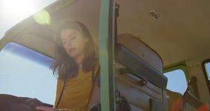 Opinión de ángulo bajo la mujer que usa el teléfono móvil en la furgoneta 4k almacen de video