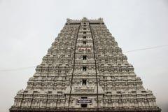 Opinión de ángulo bajo de la parte delantera de Raja Gopuram del templo de Thiruvannamalai con un cielo nublado en el fondo imagen de archivo