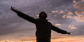 Opinión de ángulo bajo de la situación del hombre joven debajo del cielo de la tarde que brilla intensamente imagen de archivo