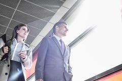 Opinión de ángulo bajo los hombres de negocios que caminan en la estación de ferrocarril Imagen de archivo libre de regalías