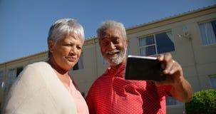 Opinión de ángulo bajo de los pares mayores afroamericanos activos que toman el selfie con el teléfono móvil en el Garde almacen de metraje de vídeo