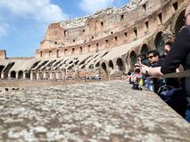 Opinión de ángulo bajo turistas dentro del Colosseum durante el día con las cámaras Imagenes de archivo