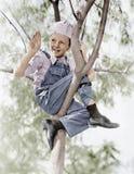 Opinión de ángulo bajo un muchacho que se sienta en un árbol (todas las personas representadas no son vivas más largo y ningún es foto de archivo
