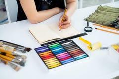 Opinión de ángulo del primer de un proyecto femenino del dibujo del pintor en el sketchbook usando el lápiz Artista que bosqueja  Foto de archivo libre de regalías