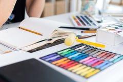 Opinión de ángulo del primer de un proyecto femenino del dibujo del pintor en el sketchbook usando el lápiz Artista que bosqueja  Imagenes de archivo