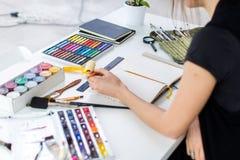Opinión de ángulo del primer de un proyecto femenino del dibujo del pintor en el sketchbook usando el lápiz Artista que bosqueja  Imagen de archivo