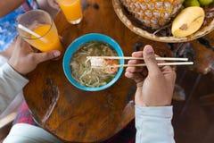 Opinión de ángulo superior el palillo antropófago de los tallarines y Juice Trying Traditional Asian Food anaranjado de consumici Foto de archivo libre de regalías
