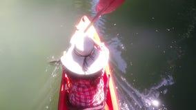 Opinión de ángulo superior la mujer Kayaking en la cámara POV de la acción de la laguna de la muchacha que se bate en el barco de metrajes