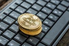 Opinión de alto ángulo de cuatro bitcoins de oro en un teclado imagenes de archivo