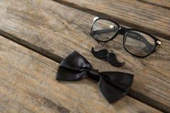Opinión de alto ángulo de la corbata de lazo con el bigote y las lentes en la tabla Fotos de archivo