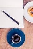 Opinión de alto ángulo de la pluma en la libreta por la comida y el café en la tabla Foto de archivo libre de regalías