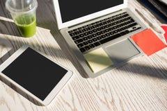 Opinión de alto ángulo de la tableta con el ordenador portátil en el escritorio en la oficina Fotos de archivo libres de regalías