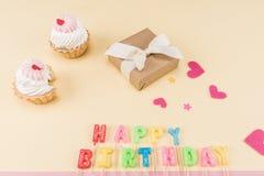 Opinión de alto ángulo de las letras del feliz cumpleaños, de las tortas y de la caja de regalo en beige Foto de archivo libre de regalías