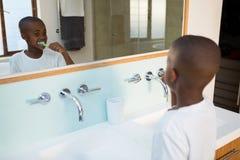 Opinión de alto ángulo de los dientes de cepillado del muchacho vistos de la reflexión de espejo imagen de archivo