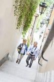 Opinión de alto ángulo de los pares de mediana edad que llevan a cabo las manos mientras que sube camina al aire libre Imágenes de archivo libres de regalías