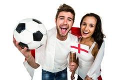 Opinión de alto ángulo de los pares que sostienen fútbol y la bandera inglesa Fotos de archivo