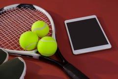Opinión de alto ángulo de los zapatos de los deportes y de la tableta digital por las bolas en la estafa de tenis Fotografía de archivo