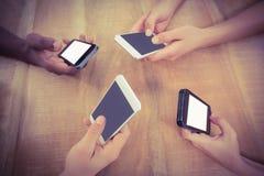 Opinión de alto ángulo de manos cosechadas usando los teléfonos móviles en el escritorio fotos de archivo libres de regalías