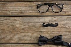 Opinión de alto ángulo del bigote con las lentes y la corbata de lazo en la tabla Fotografía de archivo