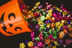 Opinión de alto ángulo del cubo con los chocolates coloridos durante Halloween Fotos de archivo