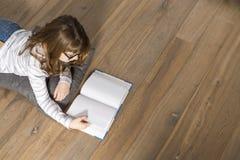 Opinión de alto ángulo del libro de lectura del adolescente en piso en casa Foto de archivo