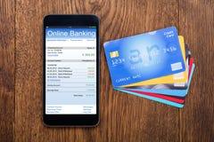 Opinión de alto ángulo del móvil con la tarjeta de crédito imágenes de archivo libres de regalías